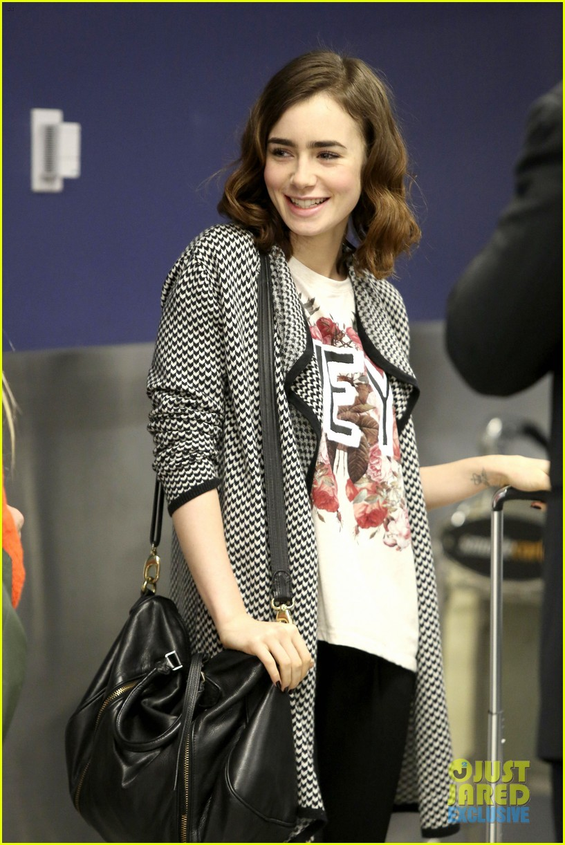 lily collins pushes giant luggage cart after mortals tour 042939605
