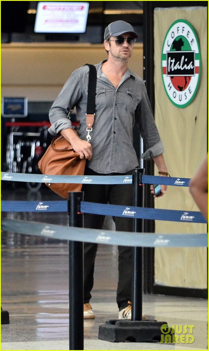gerard butler ducks under ropes at barbados airport 01