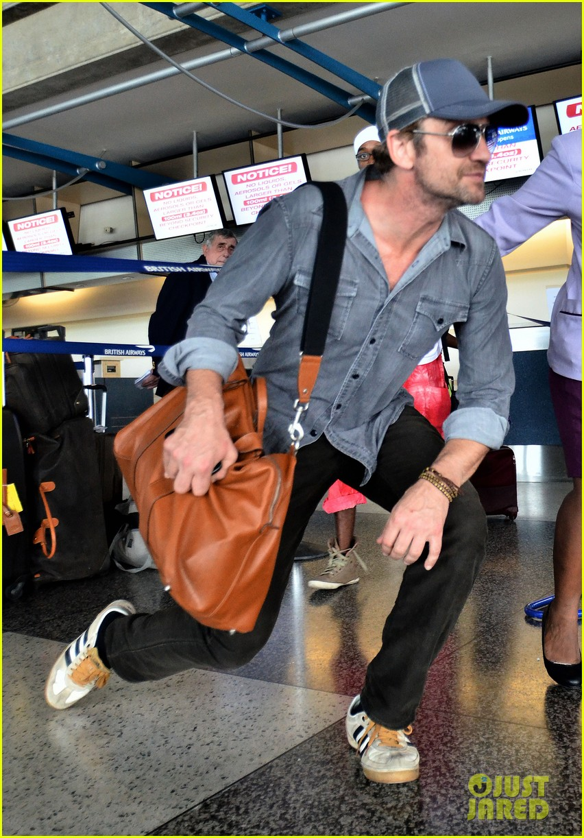 gerard butler ducks under ropes at barbados airport 03