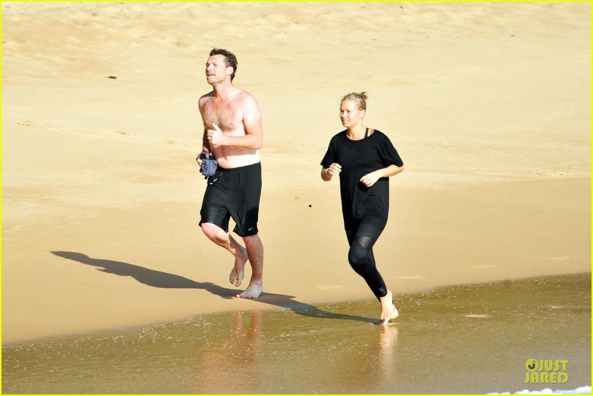 shirtless sam worthington laura bingle beach kissing couple 18