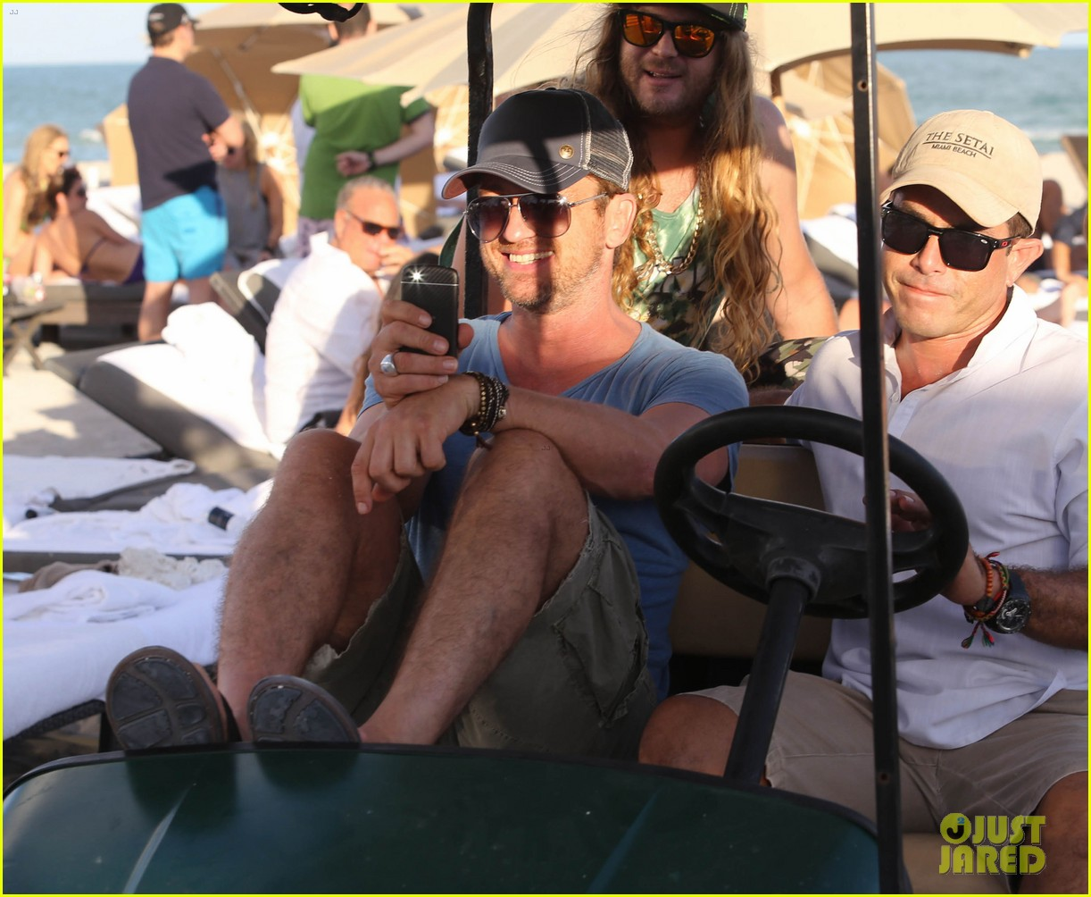 gerard butler kicks back takes photos during golf cart ride 163006672
