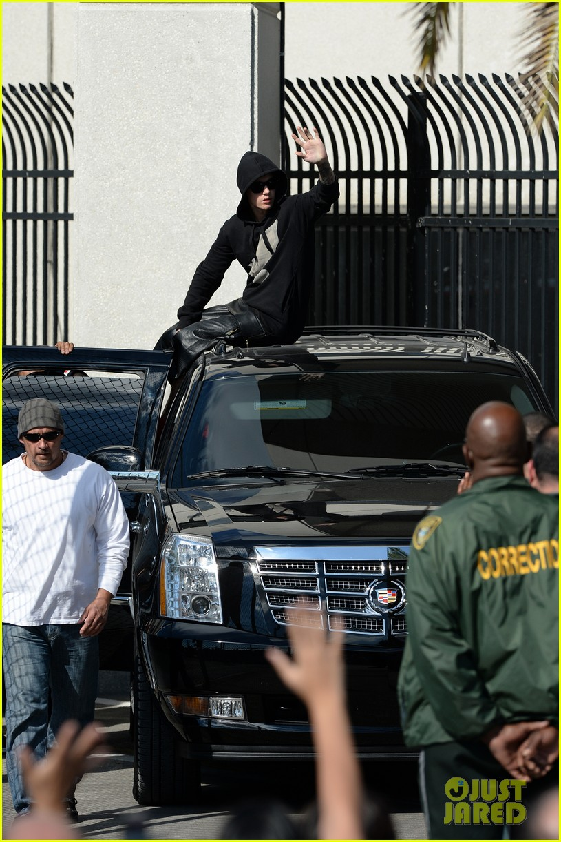 justin bieber leaves jail waves to fans after arrest 03