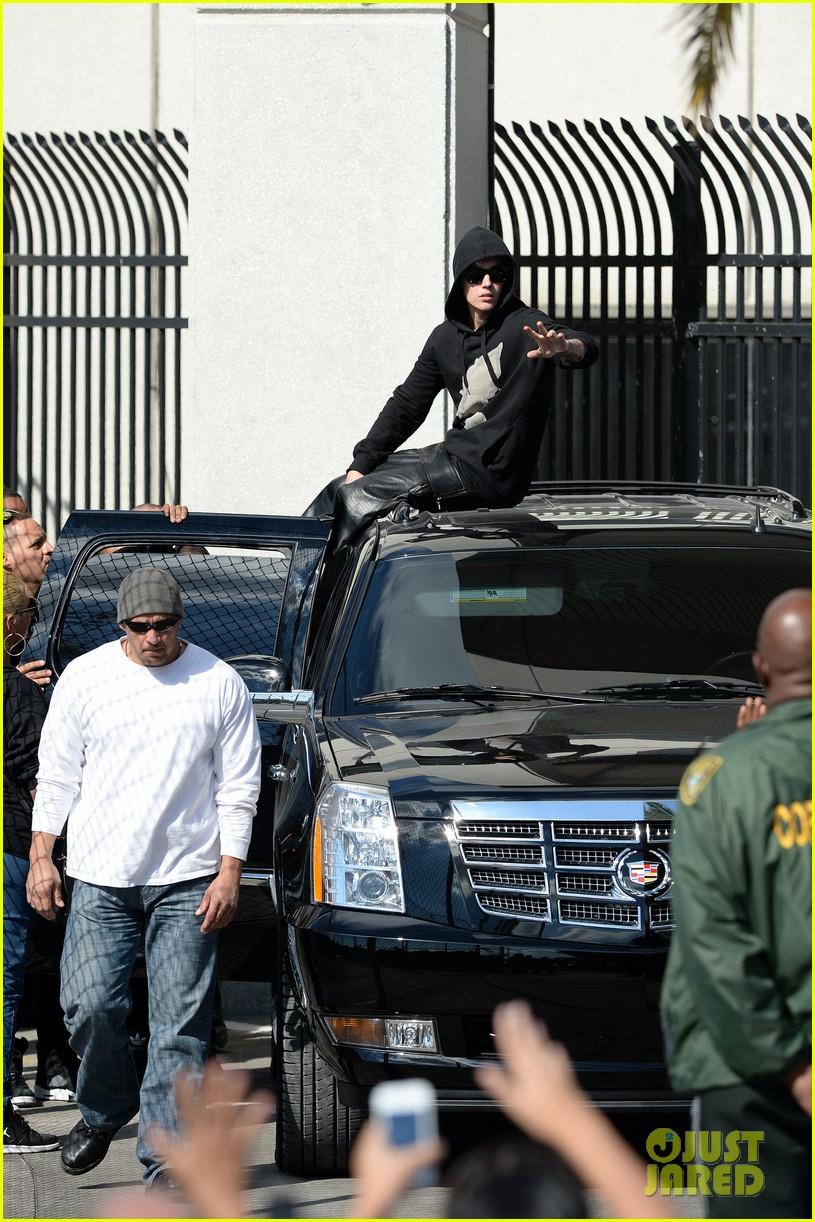 justin bieber leaves jail waves to fans after arrest 08