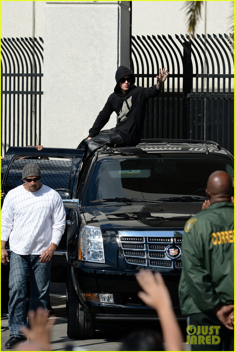 justin bieber leaves jail waves to fans after arrest 09