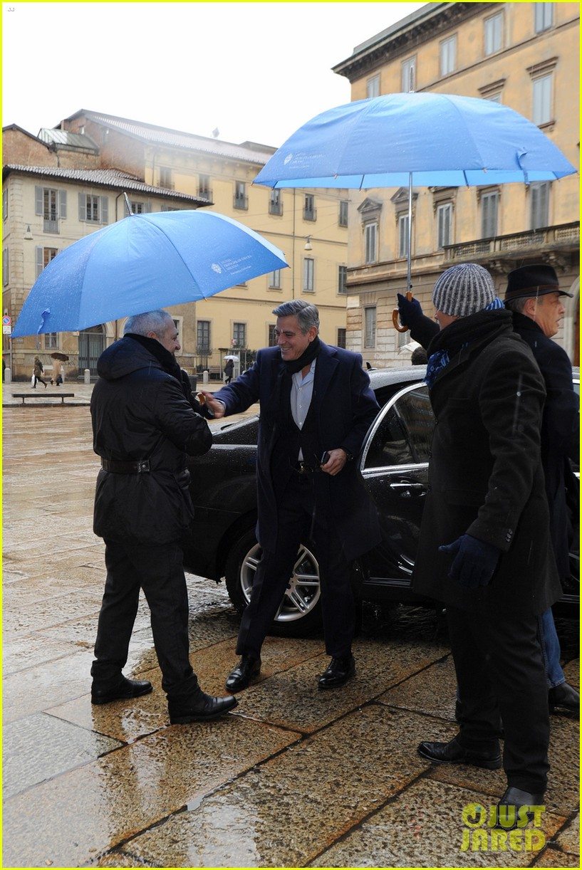 matt damon george clooney get personal umbrella holders in milan 093050717