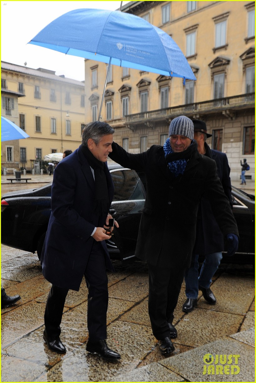 matt damon george clooney get personal umbrella holders in milan 123050720