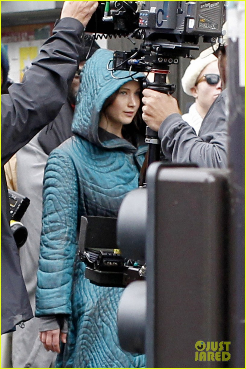 jennifer lawrence covers up her costume for hunger games 03