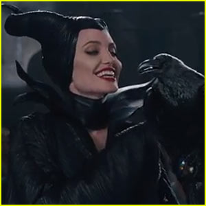 A raven, Diaval, is looking with his beak open at Angelina Jolie in an all black Maleficent costume (including seamless horns and the classically represented raised collar). She is smiling at him, and perhaps he is smiling back.