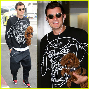 Orlando Bloom Lands Back in LA with Pup in Hand (& On Shirt)
