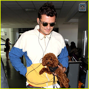 Orlando Bloom Carries His Cute Dog Through the Airport