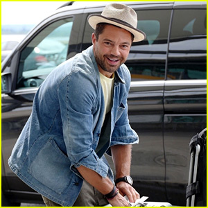 Dominic Cooper Flashes a Smile While Handling His Luggage at Heathrow