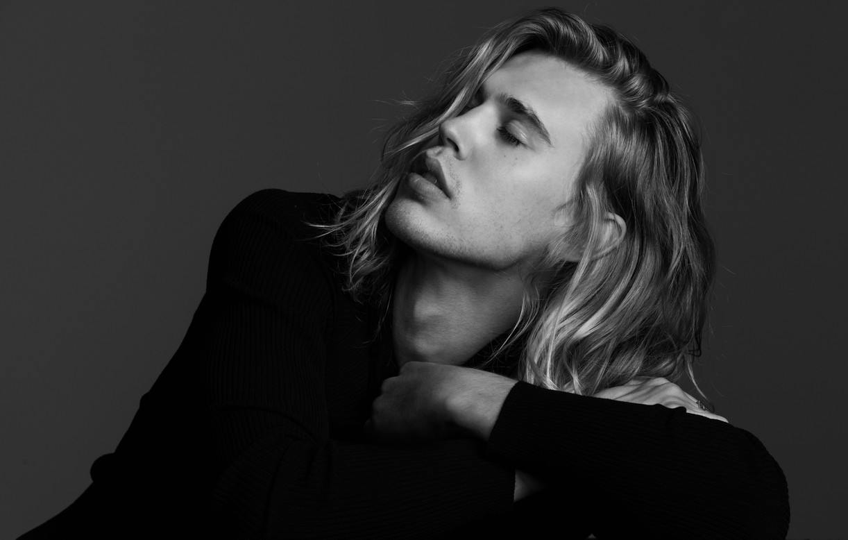 Austin Butler with his long hair covering half his face