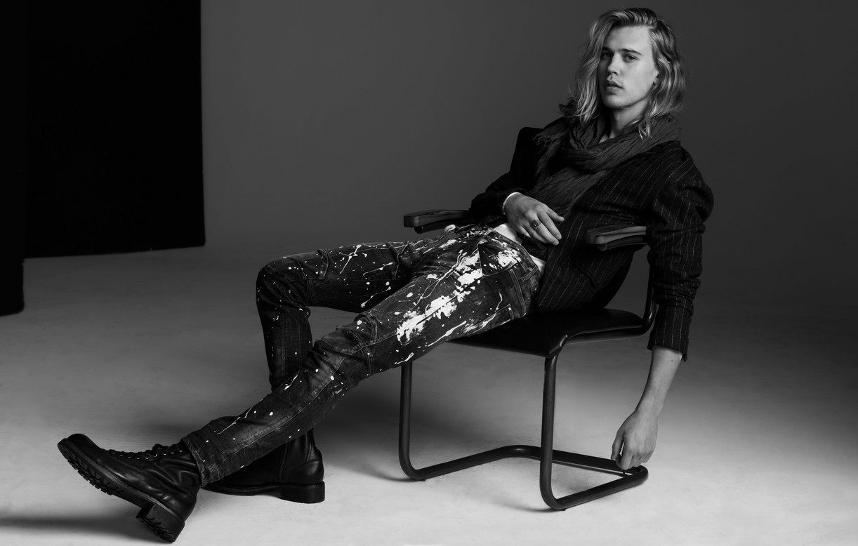 Austin Butler sitting in a chair while wearing paint-covered pants
