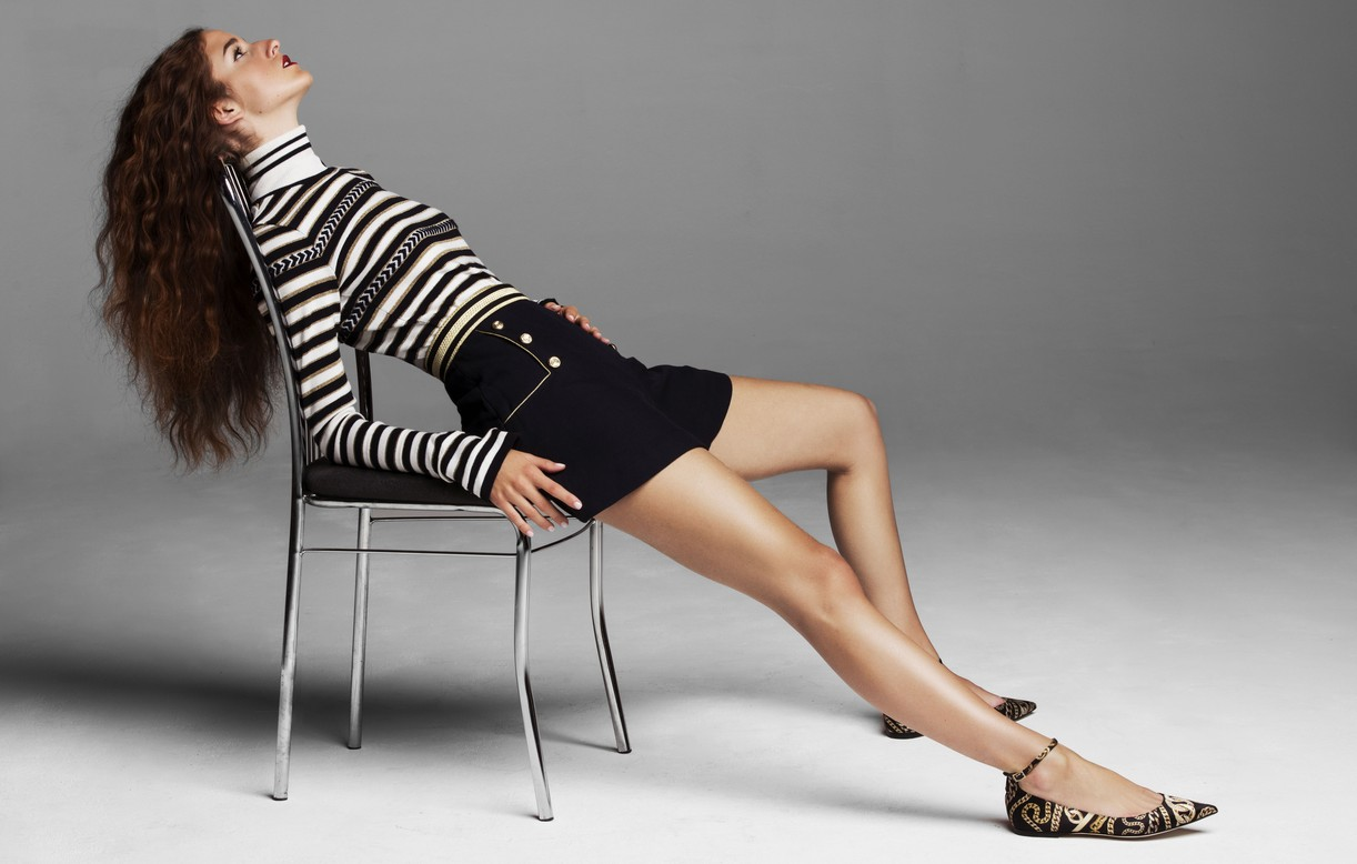 Coco Konig relaxes in a chair while wearing a black and white outfit