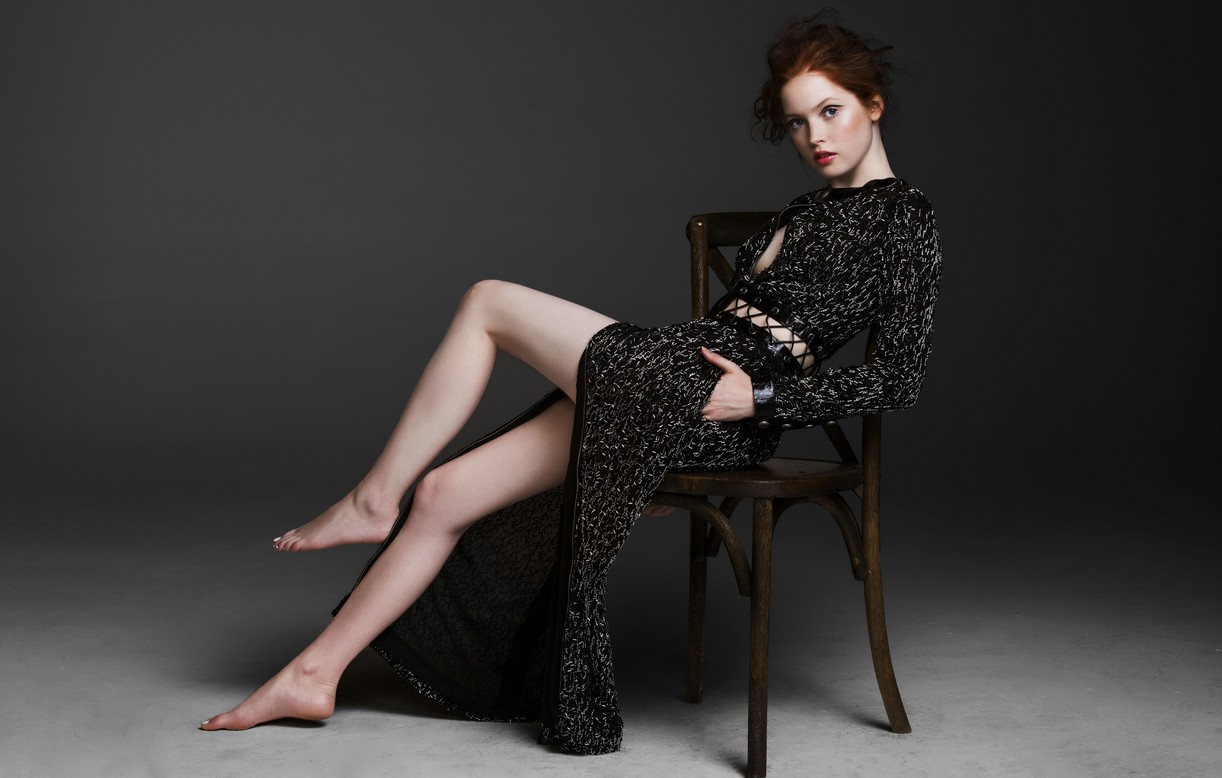Ellie Bamber sits in a chair and bares a lot of leg