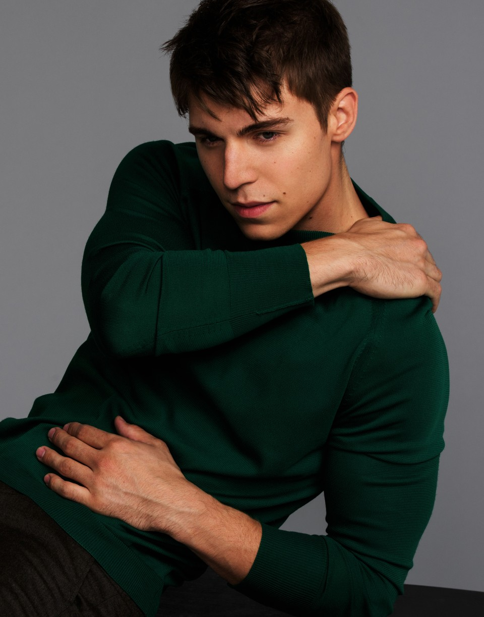 Nolan Funk wearing a green sweater with one hand on his shoulder